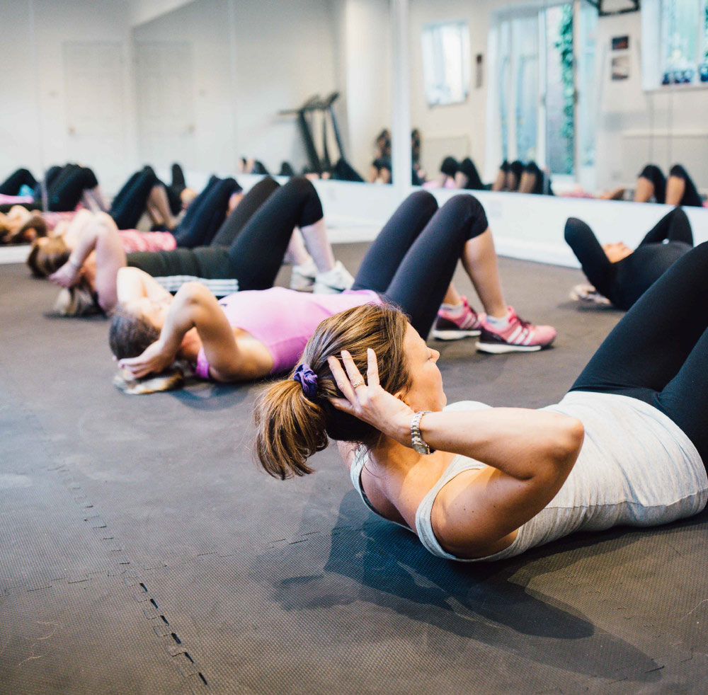 A group of women doing stomach crunches