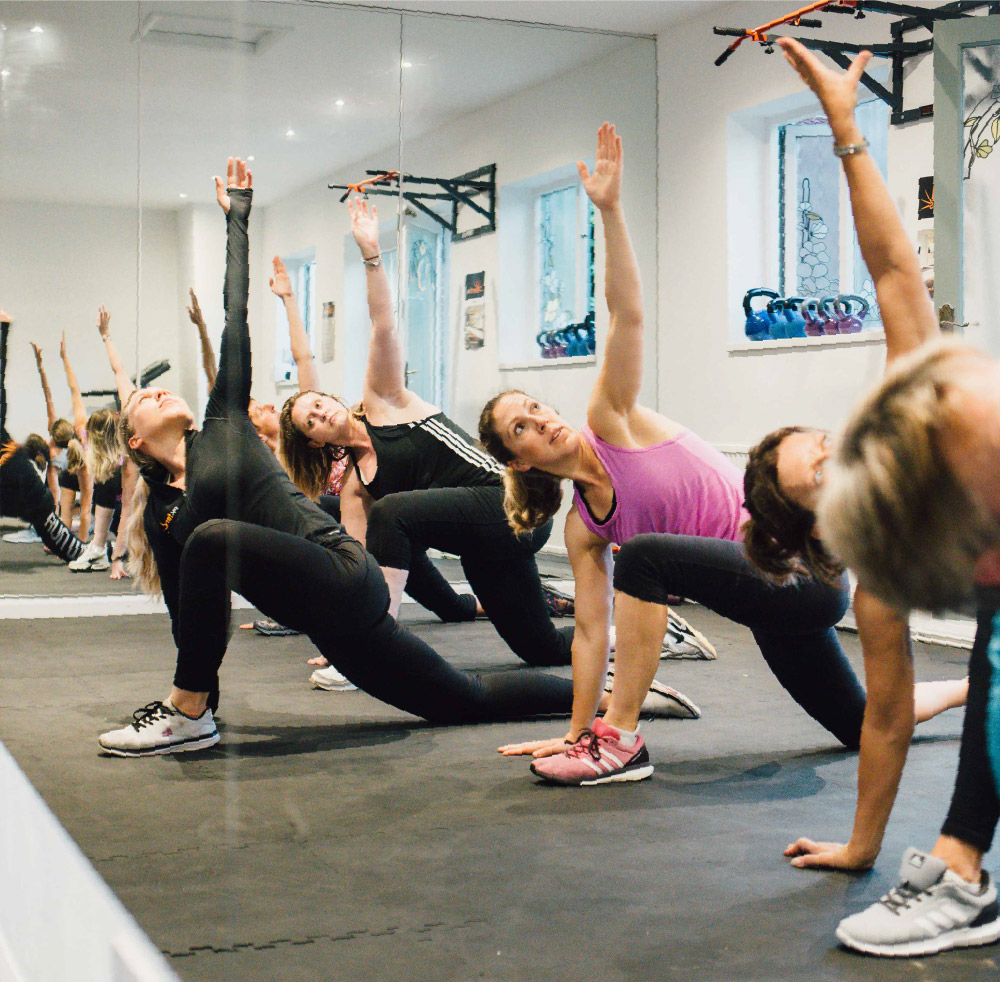 A group of women in a class doing arm and core stretches